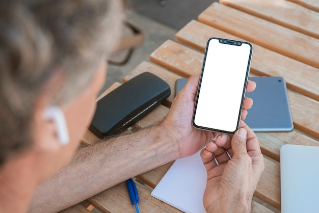 Close-up of man looking at cellphone with blank white screen Free Photo