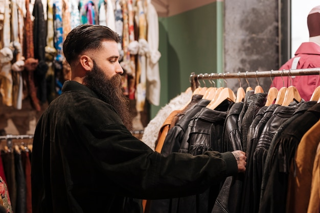 Close-up of a man looking at the leather jacket on the rail in the clothing shop Free Photo