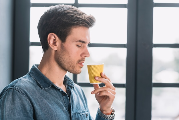 Close-up of a man looking at take away coffee cup in hand Free Photo