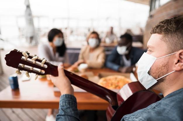 Крупным планом человек играет на гитаре за столом Бесплатные Фотографии