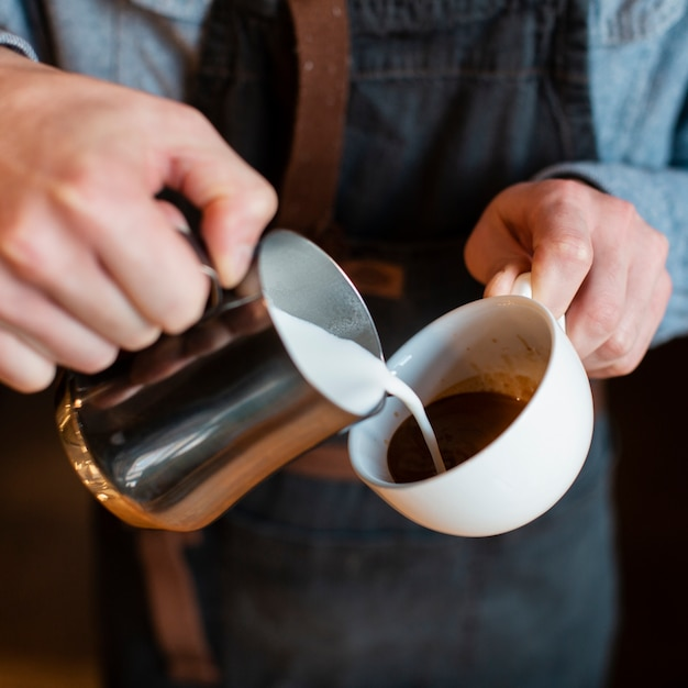 Close-up of man pouring milk in cup of coffee Free Photo