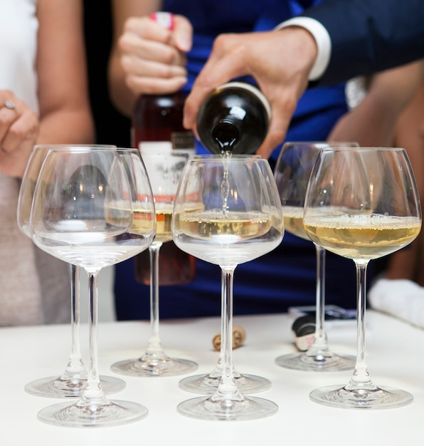 Close-up of man pouring white wine Free Photo