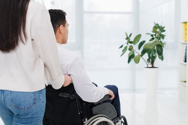 Close-up of a man pushing a woman in a wheelchair Free Photo