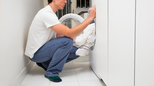 Close-up of a man putting clothes in the washing machine Free Photo