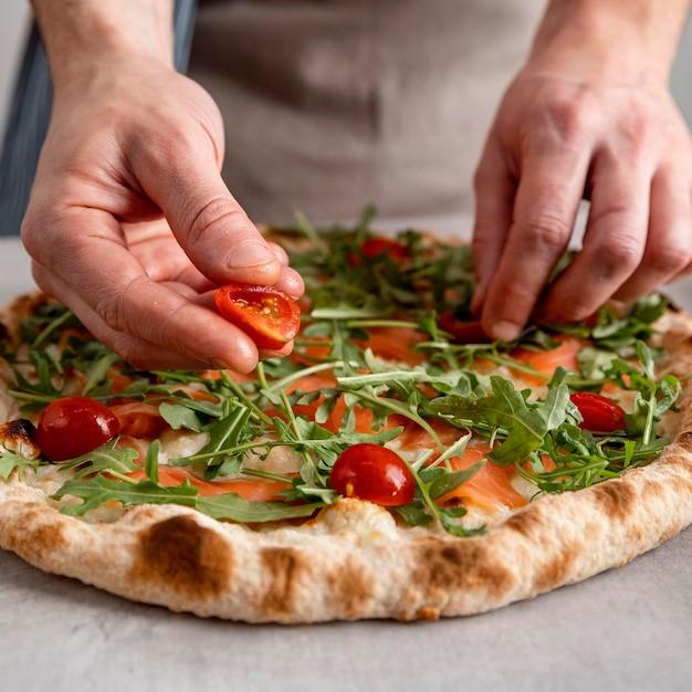 Мужчина крупным планом кладет помидоры на тесто для запеченной пиццы с ломтиками копченого лосося Бесплатные Фотографии