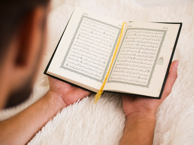 Close up of man reading from quran Free Photo