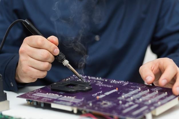 Мужчина крупным планом ремонтирует материнскую плату компьютера Premium Фотографии