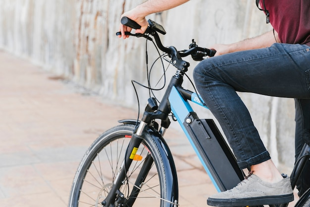 Close up man riding an e-bike Free Photo