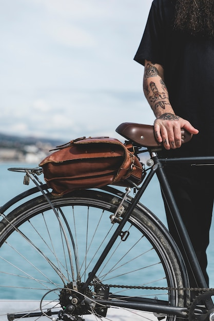 Close-up of man's hand on bicycle with brown bag Free Photo