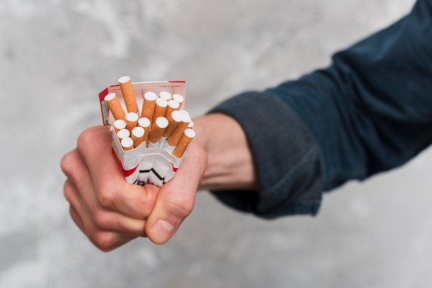Close-up of man's hand crushing cigarettes box Free Photo