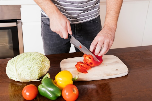 Close-up of a man's hand cutting the red bellpepper with sharp knife on chopping board Free Photo
