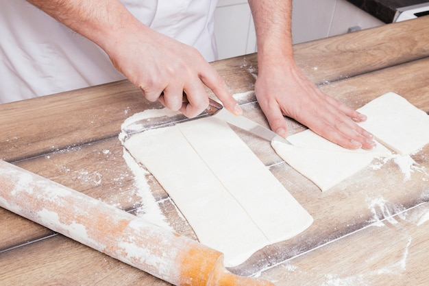 Close-up of man's hand cutting the rolled dough with knife on table Free Photo