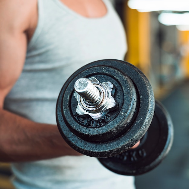 Close-up of a man's hand doing exercise with dumbbells Free Photo