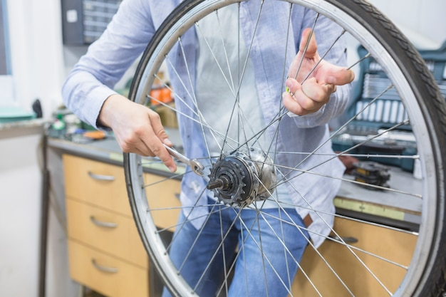 Close-up of a man's hand fixing bicycle tire with wrench Free Photo