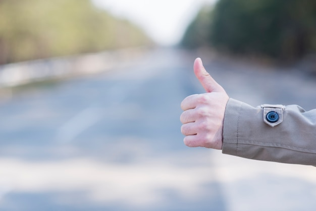 Close-up of man's hand hitchhiking at countryside road Free Photo