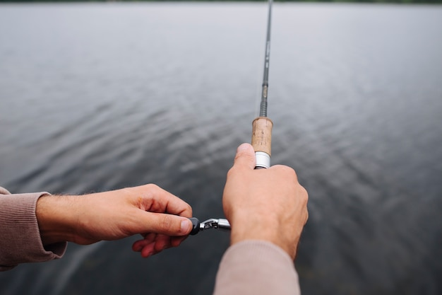 Close-up of man's hand holding fishing rod over the lake Free Photo