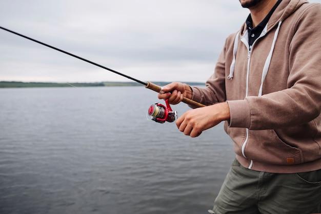 Close-up of man's hand holding fishing rod near the lake Free Photo
