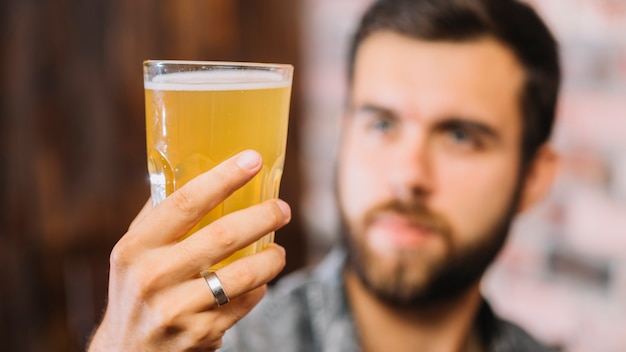 Close-up of a man's hand holding glass of beer Free Photo
