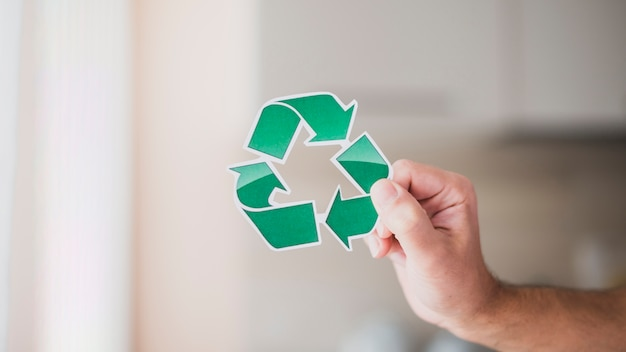 Close-up of man's hand holding green recycle icon Free Photo
