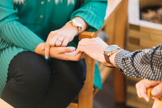 Close-up of man's hand holding his girlfriends hand sitting on chair Free Photo