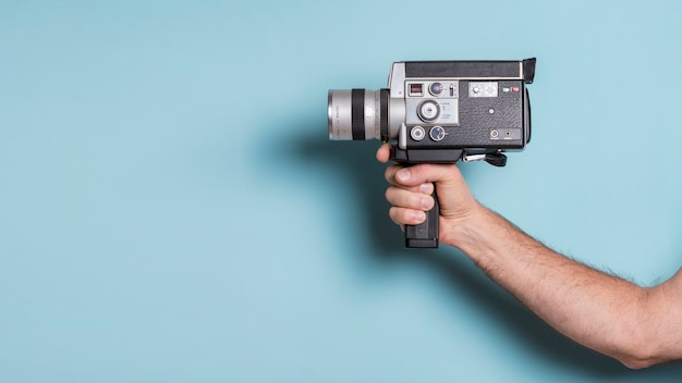Close-up of man's hand holding old-fashioned camcorder against blue background Free Photo