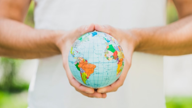 Close-up of man's hand holding small globe Free Photo