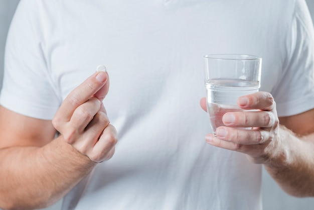 Close-up of a man's hand holding white pill and glass of water in hand Free Photo