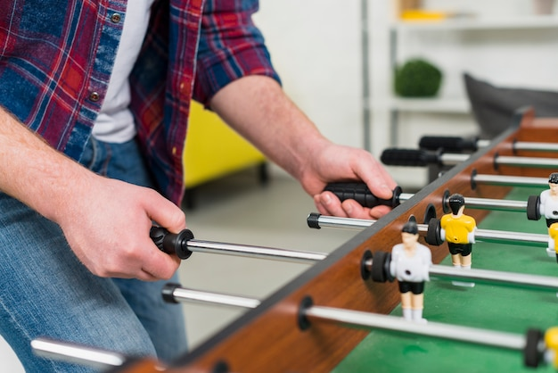 Close-up of man's hand playing the football table soccer game Free Photo