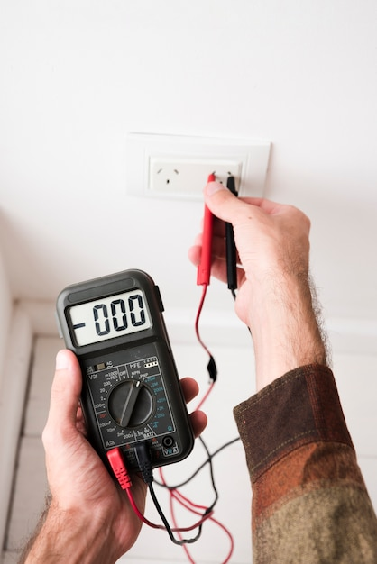 Close-up of man's hand plugging digital multimeter in plug at home Free Photo