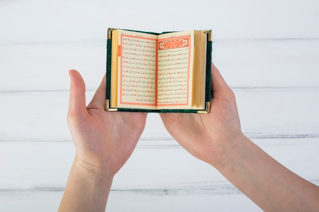 Close-up of a man's hand reading quran over the white wooden table Free Photo