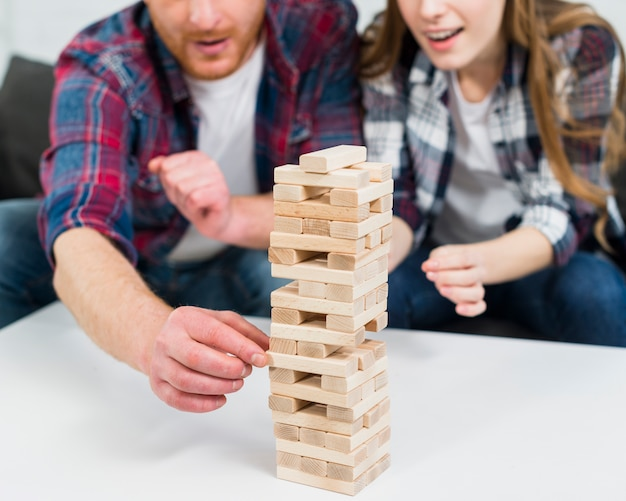 Close-up of man's hand removing the wooden blocks from the tower on white table Free Photo