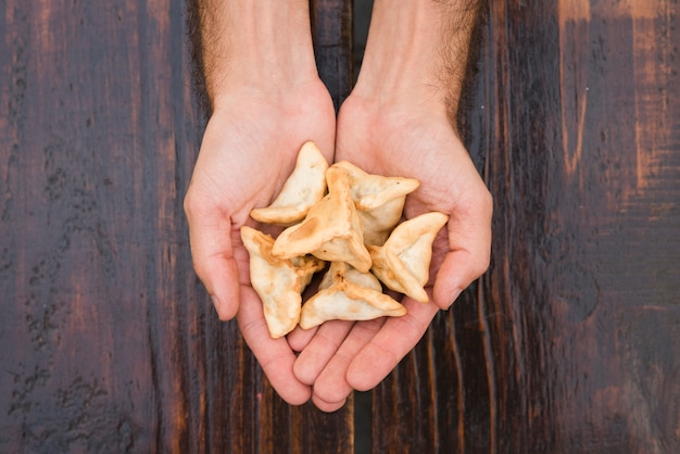 Close-up of a man's hand showing dumplings against wooden texture backdrop Free Photo