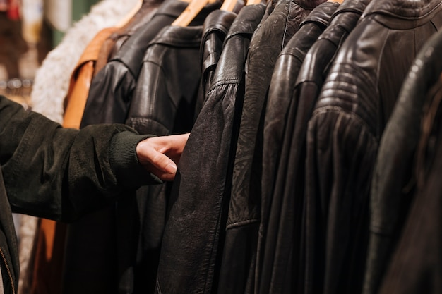 Close-up of a man's hand touching the black leather jacket on the rail in the clothes store Free Photo
