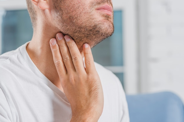 Close-up of a man's hand touching his throat Premium Photo
