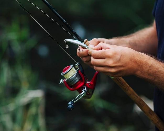 Close-up of man's hand tying fishing hook Free Photo