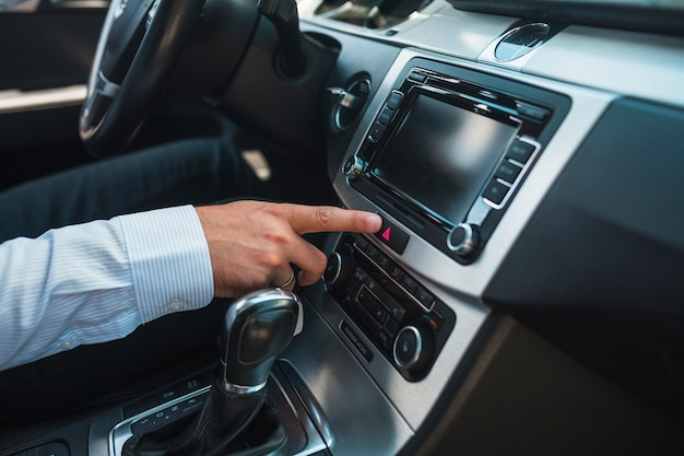 Close-up of a man's hand using car audio stereo system Free Photo