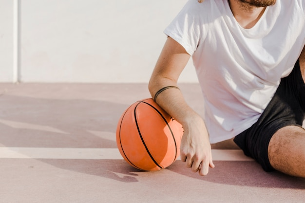 Close-up of a man's hand with basketball in court Free Photo