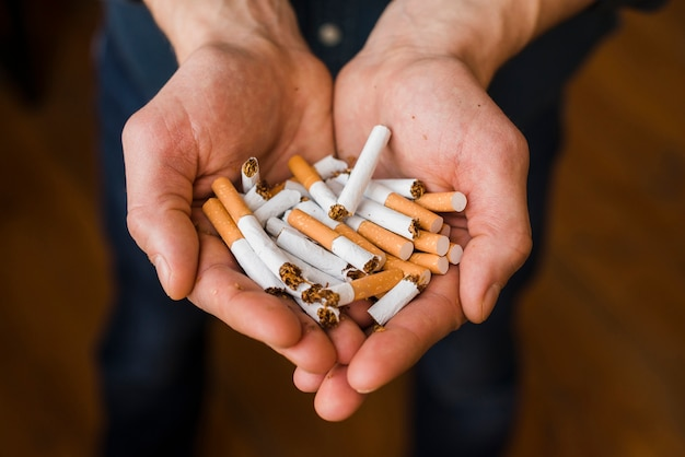 Close-up of man's hand with bunch of breaking cigarette Free Photo