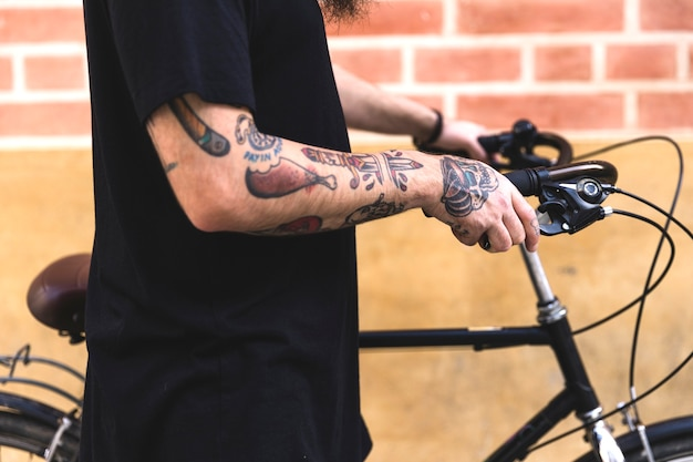 Close-up of man's hand with tattoo holding bicycle in front of wall Free Photo