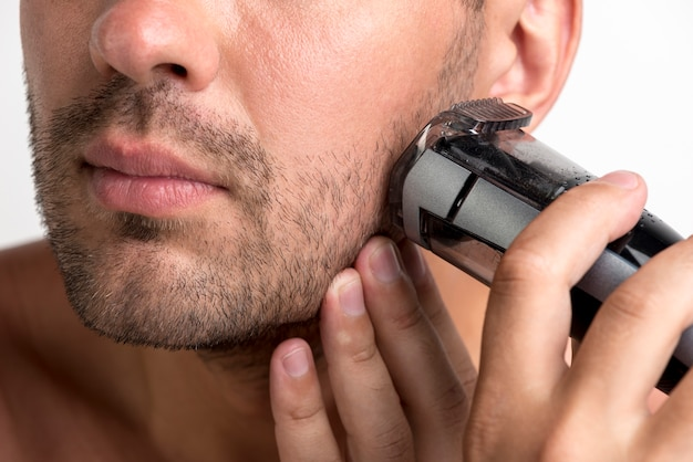 Close-up of man shaving with black trimmer Free Photo