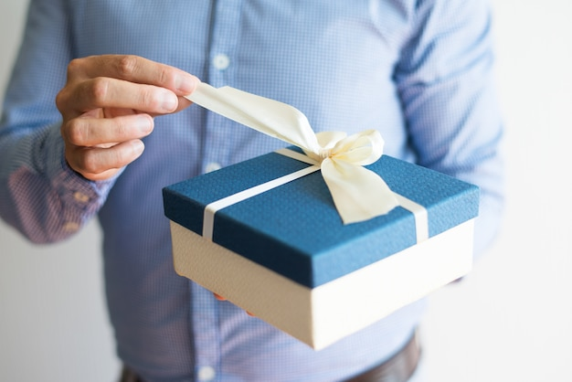 Close-up of man in shirt opening birthday gift Free Photo