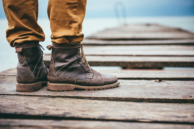 Close up on man standing on dock and wearing leather boots Premium Photo