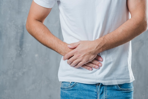 Close-up of a man suffering from abdominal pain Free Photo