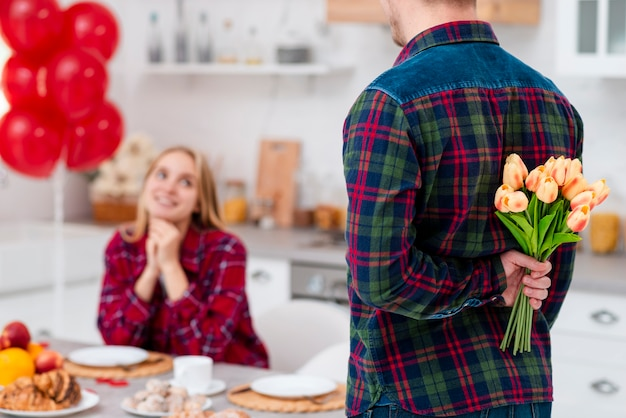 Close-up man surprising woman with flowers Free Photo