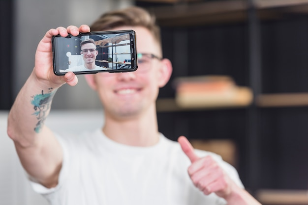 Close-up of a man taking selfie on mobile phone showing thumb up sign Free Photo