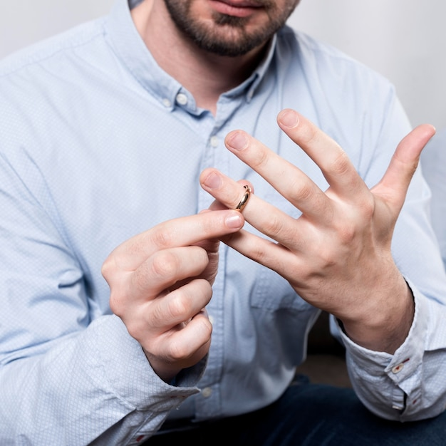 Close-up man taking wedding ring off finger Free Photo