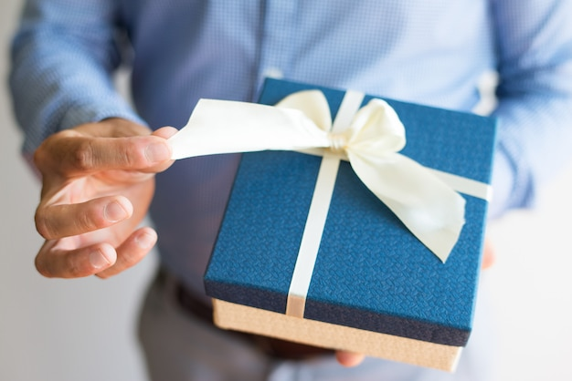 Close-up of man untying bow while opening gift Free Photo