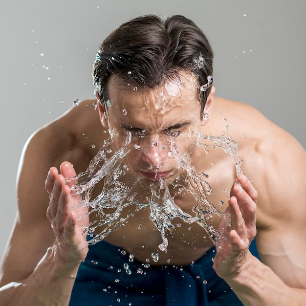Close up man washing his face with water Free Photo