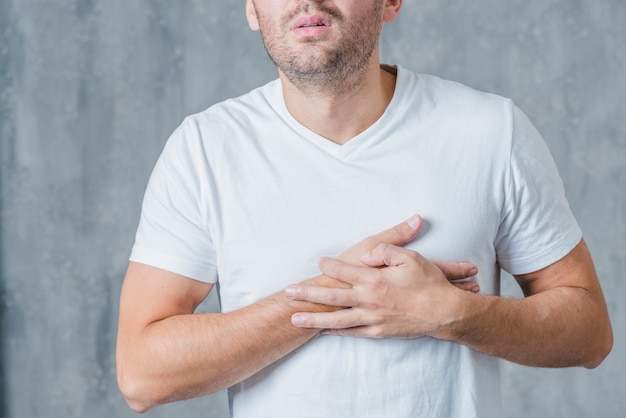Close-up of a man in white t-shirt having heart pain Free Photo