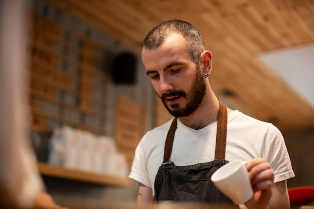Close-up of man with apron holding on empty cup Free Photo